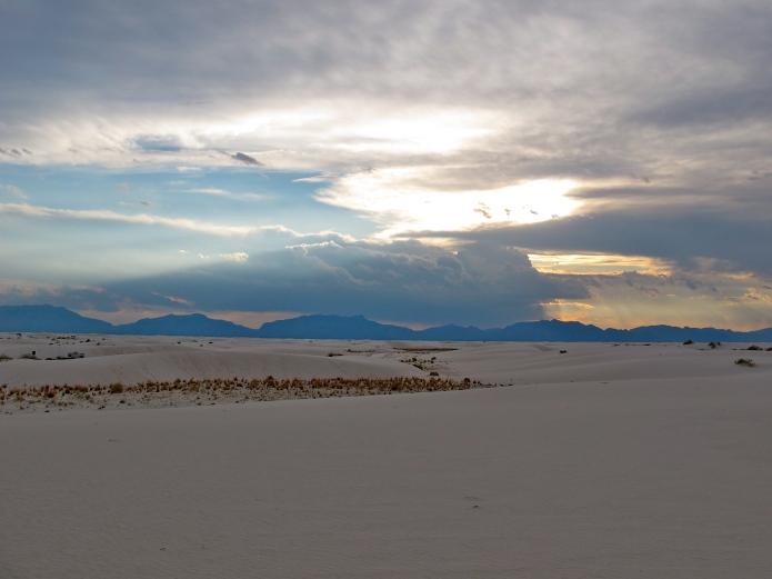 The rain clouds were rolling in as the sun set in White Sands, creating beautiful god clouds over the mountains.